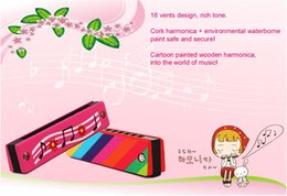 Children painted wooden toy harmonica. Creative enlightenment educational toys musical instruments. Multicolor green parenting aids