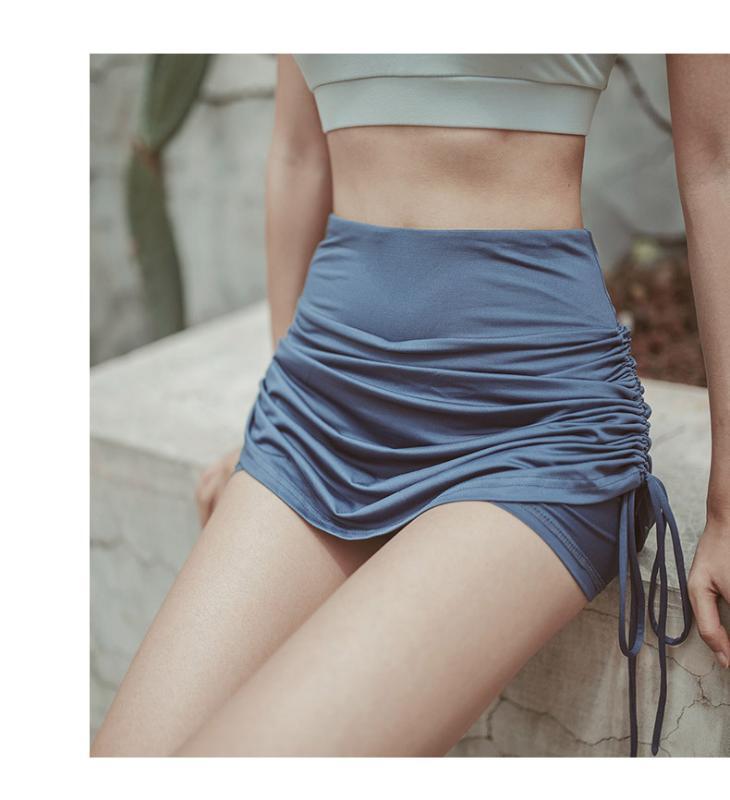 Mujeres pantalón corto deportivo ejecutan pantalón corto deportivo contra la luz falda de los deportes atractivos de las mujeres de cintura alta