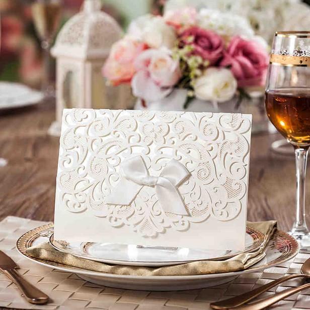 熱い販売パーソナライズされた結婚式の招待状カードアイボリーの色、美しいレーザーカット中空の植物とリボンのエレガントなパーティーカード