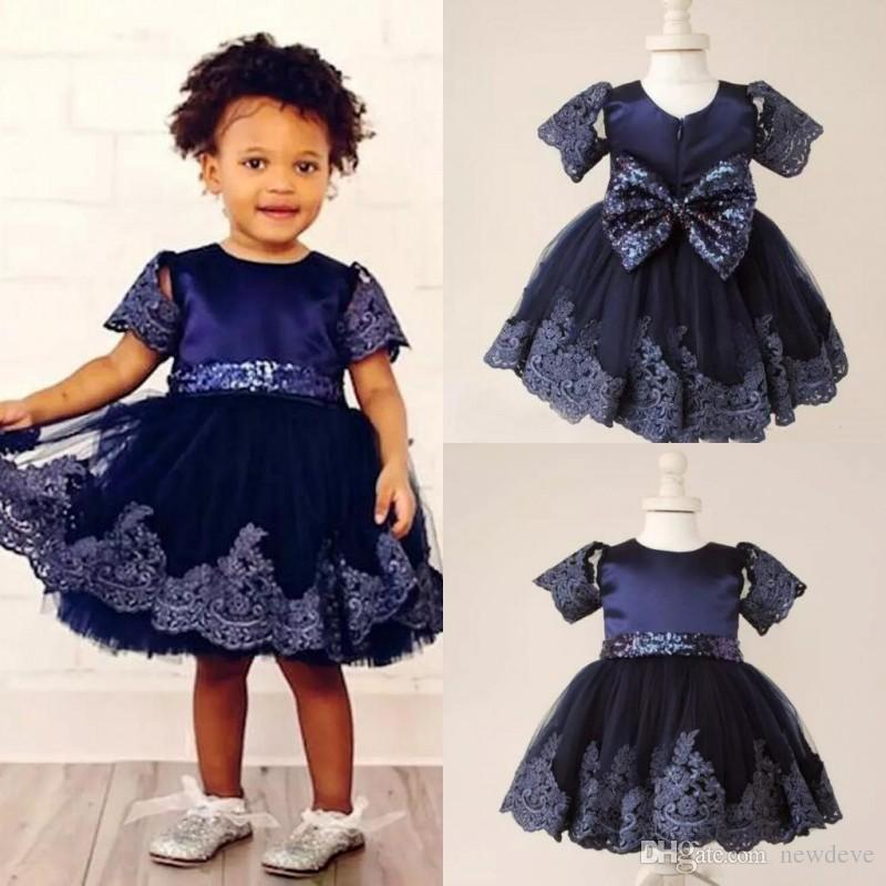 Le ragazze di fiore dell'abito di sfera del pizzo del blu marino si vestono per i vestiti di comunione di paillettes del paillettes di lunghezza di ginocchio con le maniche Grande arco indietro