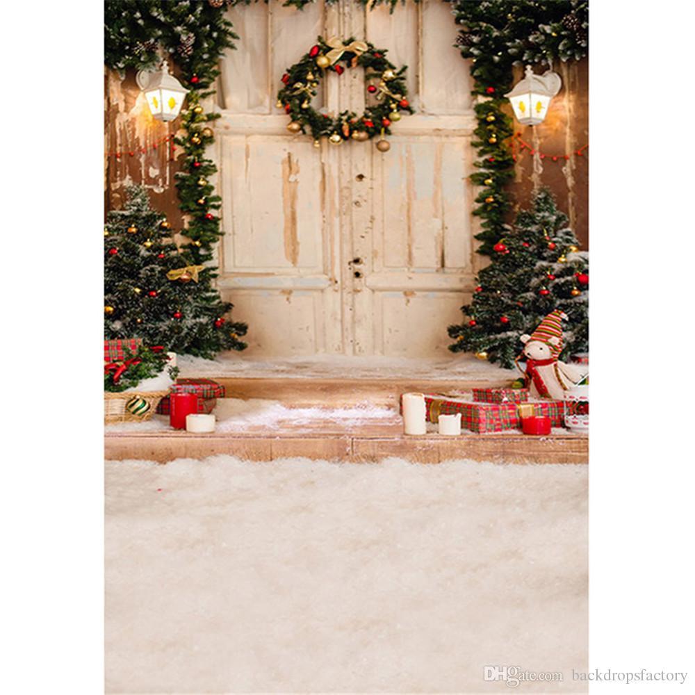 في الهواء الطلق منزل شجرة عيد الميلاد التصوير خلفية اكليلا من الزهور على الباب الخشبي الأبيض علب الهدايا الأطفال الصغار الشتاء الثلوج خلفية الصورة