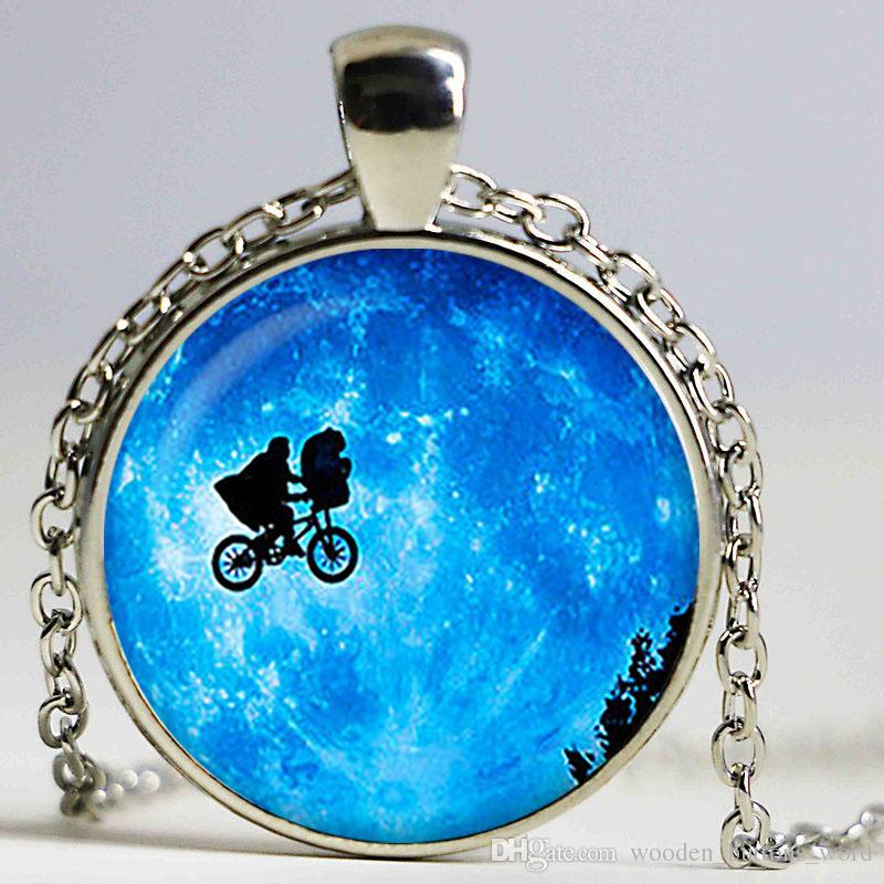 Elliott and E. T. in front of the Moon Glass pendant. Planet necklace. Space, universe jewelry,glass cabochon pendant