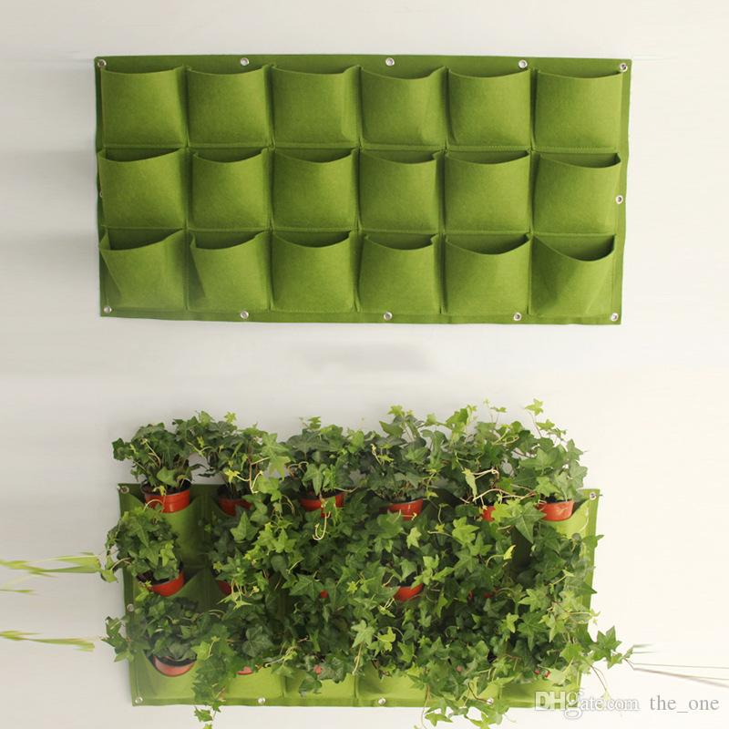 Una piantatrice di vasi da fiori tascabili su appeso a parete verticale in feltro pianta da arredamento verde campo coltiva borse per container all'aperto