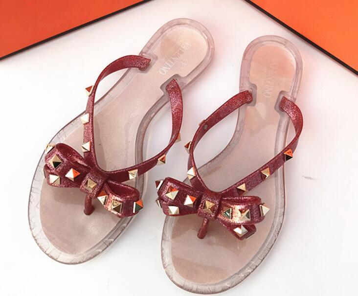 Sommer-Strand-Frau Flip Flops PVC Folien Weibliche Sandalen mit Nieten Bowknot Slip on Wohnung mit Frauen-Bolzen-Hausschuhe Gelee Schuhe