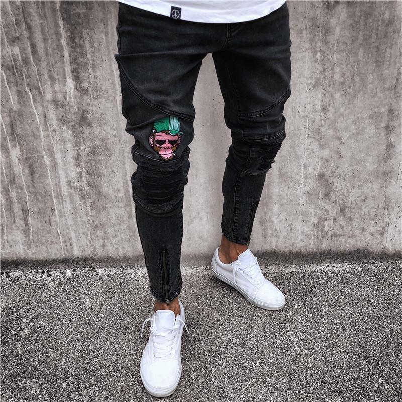 Fashion-Mens Jeans Stretchy Ripped Skinny Biker Jeans Patrón de dibujos animados destruido con cinta Slim Fit Pantalones de mezclilla negros Venta caliente
