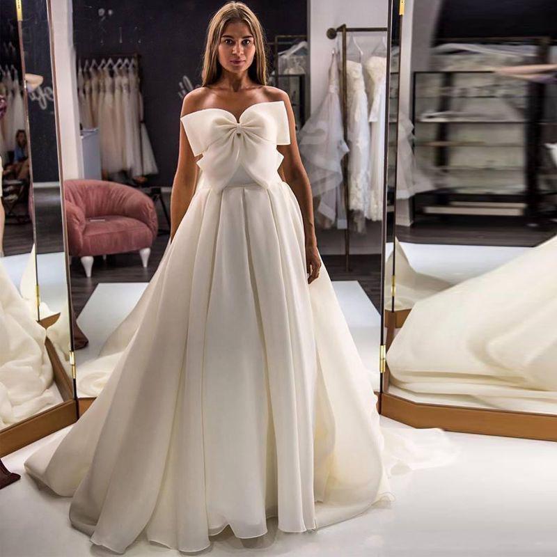 Элегантный выполненный на заказ Линия без бретелек Свадебные платья из органзы Bow Страна Свадебные платья Sweep Поезд Свадебные платья Мантия де mariée