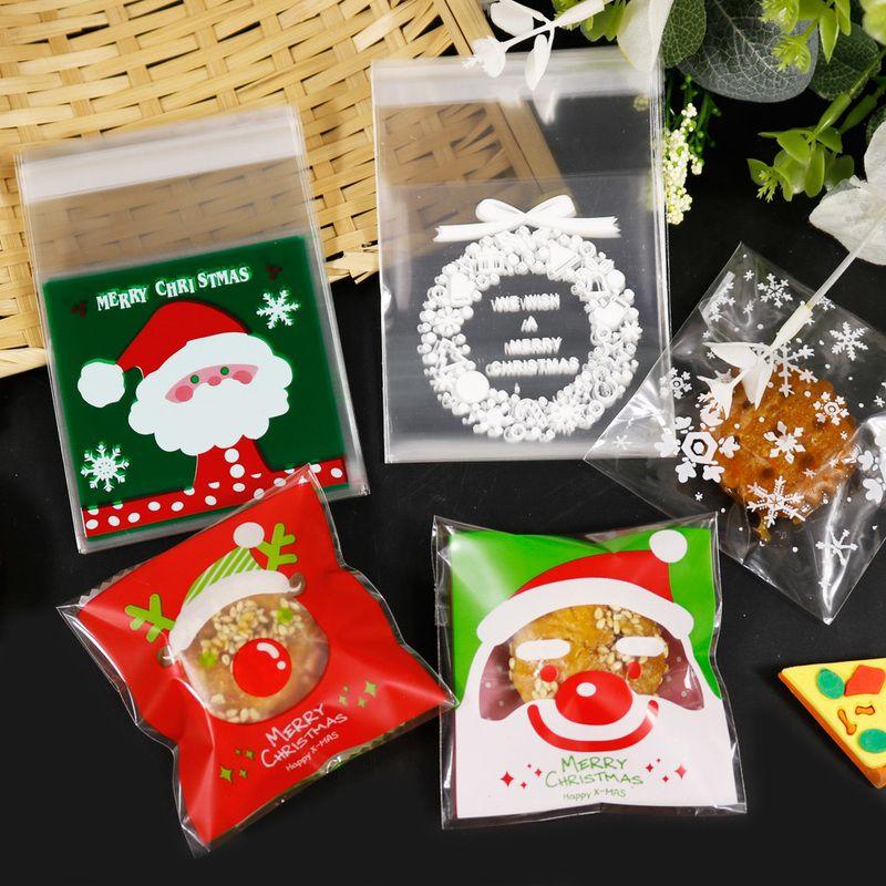 100pcs Feliz Natal saco de plástico auto-adesivo Biscoitos Doces Sacos de Papai Noel do floco de neve Xmas Presente Plastic Bags 7x7 + 3 centímetros