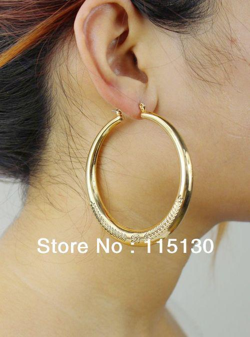 woman ear gold wonder body gld dang dangle earrings jewelry logo