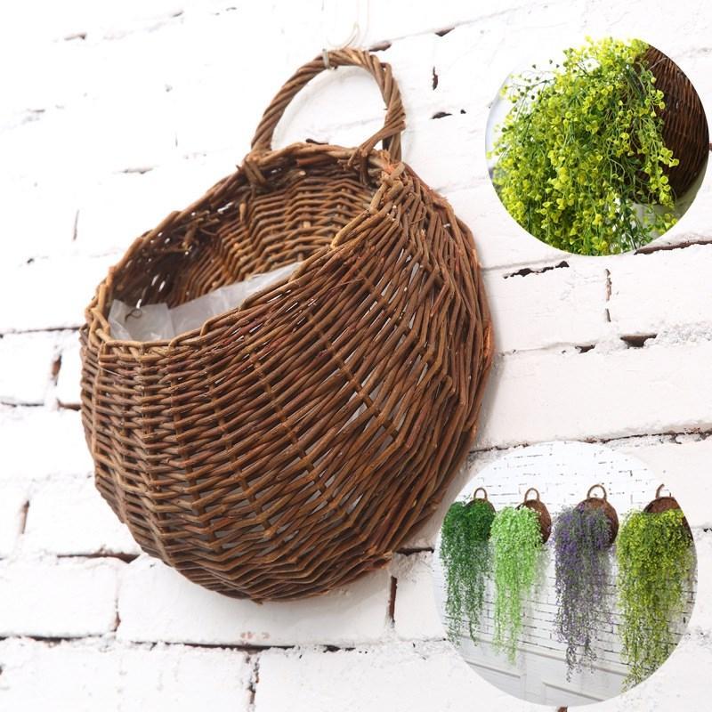 Le panier fixé au mur de fleurs artificielles suspendus à des pots de fleurs de panier de mur en osier a suspendu des jardinières pour le mariage de jardin