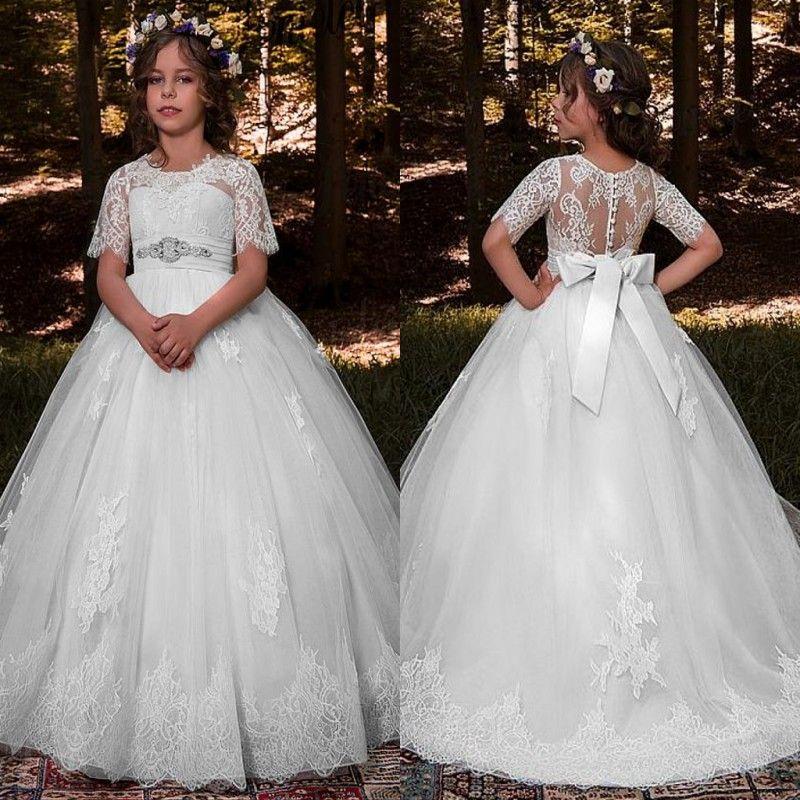 2019 Cute Holy White Flower Girl Dresses For Garden Summer Weddings Kids  Formal Wear Lace Appliques Sheer Sleeves Beaded Bow Sash