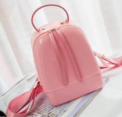 La donna bagna la mini borsa a tracolla di colore della caramella del bambino adulto dello zaino della gelatina impermeabile