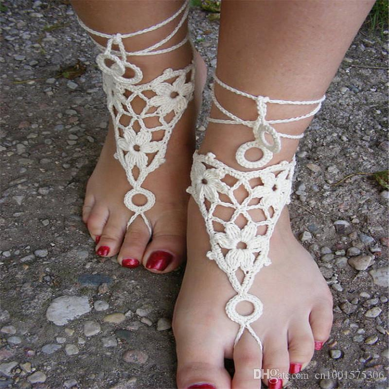 손으로 뜨개질을 한 섹시한 맨발, 백색 색깔에있는 레이스 샌들, 집시 신부 발, 순수한 면사에서 만드는.
