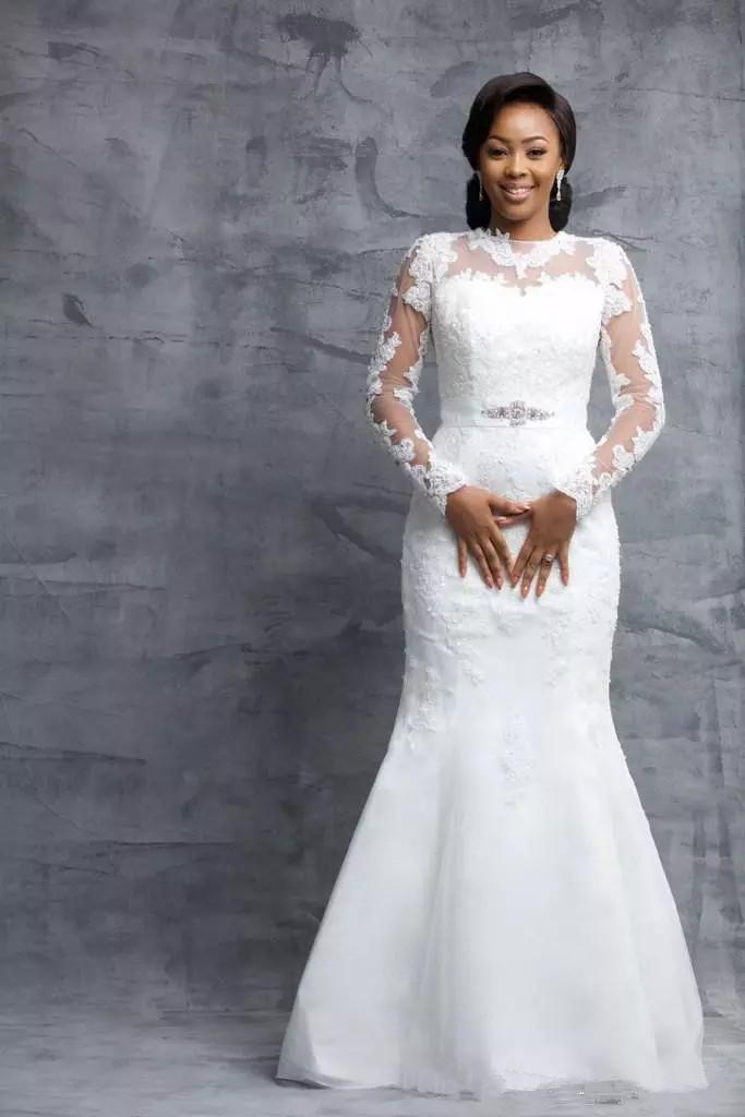 Abiti da sposa a sirena sexy Sheer Maniche lunghe Crew Appliques Abiti da sposa in pizzo nigeriano con cintura di perline Lunghezza lunga del pavimento