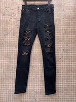 ファッションデザイナーのメンズジーンズロングパンツスキニーLeopardの穀物のスペルレザーキルトリッピングストレート穴ジーンズ男性服を破壊します