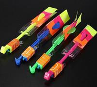 Envío gratis 12 piezas de regalo de juguete elástico Flash giratorio Flying Arrow Rocket Helicóptero de luz LED