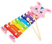 A mão livre branca dos desenhos animados de Serinette bate a música do piano. Brinquedos educativos de madeira para crianças de jardim de infância