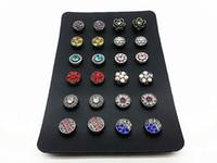 un conjunto de 12 pares de mujeres (24 piezas) mezclar 12 botones pequeños de botón a presión para pendientes con un soporte de pantalla