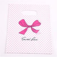 Nouveau design 100pcs / lot gros 20 * 25cm Rose Sweet Love Sacs d'emballage T-shirt en plastique Sacs avec Dot Bow