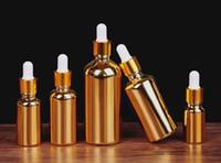 gotero para botella de aceite esencial al por mayor-Frasco gotero de vidrio de oro 50 ml 100 ml de perfume aceite esencial botella de vidrio galvanizado con tapa de aluminio y oro