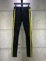 nuevos jeans amarillos para hombre al por mayor-Moda de alta calidad Nuevo estilo Denim para hombres Jean negro Pantalones con rayas amarillas Agujeros Jeans Cremallera Hombres Pantalones Pantalones