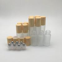 viales para aceites esenciales al por mayor-El rodillo de vidrio transparente helado embotella los recipientes de los frascos con la bola de rodillo del metal y el casquillo plástico del grano de madera para el perfume esencial 5ml 10ml del aceite