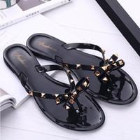 sandalias de plataforma de cuña de niña al por mayor-Remaches de las mujeres Zapatillas planas Bowknot Chanclas para niñas Zapatos de verano Zapatos de gelatina de playa Sandalias de playa Plataforma de cuña Tangas Zapatillas