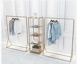 Rack per negozi online-Appendiabiti da sbarco Appendiabiti dorato nei negozi di abbigliamento Semplice esposizione di abiti da uomo e da donna