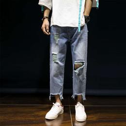 рваные джинсы корейские мужчины Скидка 2019 летние новые рваные джинсы мужчины свободные прямые трубки личности разорвал ткань корейских модных брюк прямые ноги джинсовые брюки повседневные