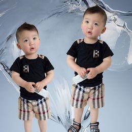 Trajes de bebé de un año online-Primavera muchacha del bebé de la tela escocesa del bolsillo de camisa de manga corta a cuadros cortos + 1-7 años traje 2pcs de los niños Niños sistemas de la ropa