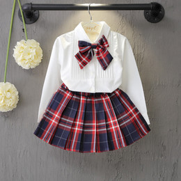 Trajes de faldas coreanas online-los niños al por menor del diseñador chándales arco de las muchachas de la camisa de tela escocesa + faldas de 2 piezas trajes trajes de manga larga de la moda coreana establecen sistemas de la ropa de los niños