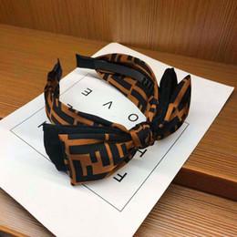 Archi coreani online-Dolce e bella bowknot fascia coreana a tesa larga fasce di tessuto dei capelli Cave dolce semplicità Nastro per capelli accessori copricapo della forcella per adulti