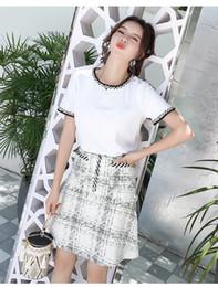 b58bec7f48 2019 nuevas tendencias moda falda Raya de flores gruesas camisetas + Botón  de borla a cuadros