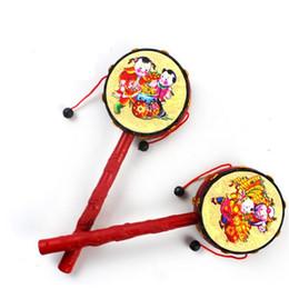 Argentina Venta al por mayor-1Pcs tradicional chino sonajero tambor juguetes giratorios para niños de dibujos animados mano de juguete de madera campana sonajero tambor de instrumentos musicales cheap chinese drum toy Suministro