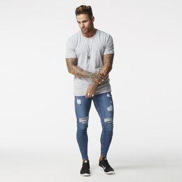 Pantalones vaqueros falsos online-Wholesale-Blue ripped Jeans para hombres Super estiramiento masculino Pant Distressed Fake Designer Brand Jeans skinny fit Style Streetwear zm02
