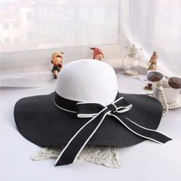 Venta caliente Moda Hepburn Viento Negro Rayado Blanco Bowknot Verano Sombrero  de Sol Mujeres Hermosas Sombrero de Playa de Paja Sombrero de Ala Grande 34994b87c502