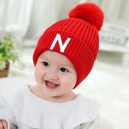 0afc4d232d420 Otoño e invierno nuevos niños colgando pelota sombrero grueso punto  esposado sombrero marca marca bola gorra bebé gorro