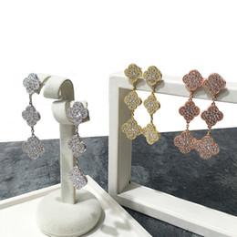 2018 Marca venta caliente Cobre chapado en oro brillante trébol de cuatro hojas Tres flores pendientes de diamantes tricolor pendientes de las mujeres encantos regalo desde fabricantes