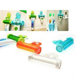 Wholesale tube squeezer toothpaste dispenser - 1 Piece Creative Rolling Squeezer Toothpaste Dispenser Tube Partner Sucker Hanging Holder
