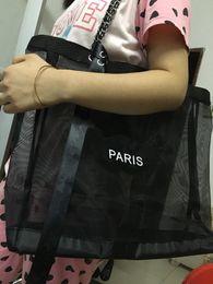 Wholesale plastic shopping - New black mesh large-capacity shopping bag to send trumpet handbag and ribbon set ladies washing or cosmetic storage beach bag VIP gift