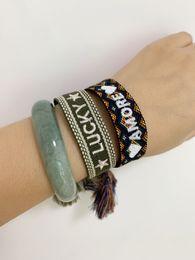 Joyas de moda de la marca a la firma de las mujeres algodón hecho a mano tejidos bordados pulsera tejida brazalete borla con cordones de la pulsera desde fabricantes