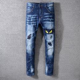 Ojos amarillos bordados del estilo de los hombres del estilo de Italia Nuevo Pantalones bordados engrasados Vaqueros pitillo azules Pantalones delgados Tamaño 29-40 # 3314 desde fabricantes