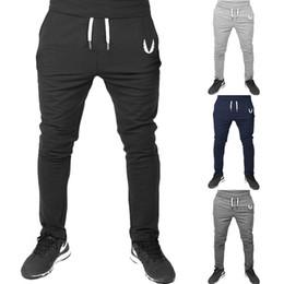 2019 pantalón de estilo urbano Pantalones de gimnasia ajustados casuales de estilo nuevo para hombres Pantalones ajustados de estiramiento bordado Pantalones deportivos deportivos de viento urbano Pantalones rectos pantalón de estilo urbano baratos