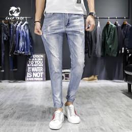 2019 hommes coréens pantalons blancs Printemps et été nouveau pantalon en denim blanc bleu clair pour hommes version coréenne du pantalon slim pour hommes, pieds élastiques promotion hommes coréens pantalons blancs
