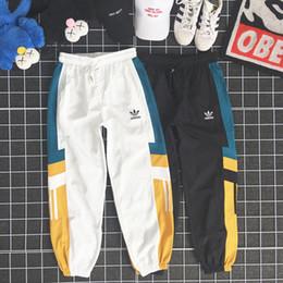 Pantalones de cordón para hombre online-Diseñador de verano Pantalones para hombre Nuevos pantalones de lujo con patrón de paneles Pantalones deportivos con cordón suelto Pantalones deportivos de nueve puntos para hombres