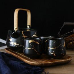 Teiere nere online-Set da tè in porcellana stile marmo d'oro con 1 teiera e 4 tazze da tè 1 vassoio in legno da tè asiatico