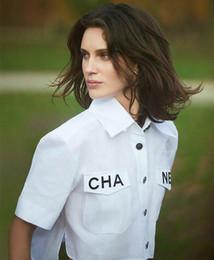 Weiße weibliche kleidhemden online-Weißes Hemd-weiblicher Swallowtail Taschen-Buchstabe-hohe Taillen-Kurzschluss-Hülsen-Nabelhemd-Fabrik-Großverkauf plus Größenkleider Bluse