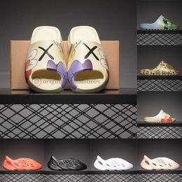Venta al por mayor de 2020 Luxe Kanye West X pintada linda diseñador dibujos animados de moda Diapositivas Hombres Mujeres espuma Runner Triple Negro Resina playa del deslizador de la sandalia pantoufle