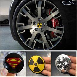 Venta al por mayor de 56mm Aluminium Superman Skull Head Cross Logo Rueda Center Hub Emblema Nuclear Radioactive Rueda Stickers Universal Fit
