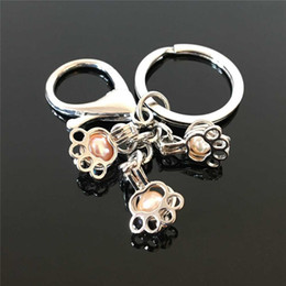 Men opening pendant online shopping - Euro American popular paw print pearl cage key ring can open hollow pearl noctilucent pearl volcanic stone pendant key ring