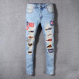 9983b1c054c Новая мужская мода Европейская и американская уличная мода рваные джинсы с  вышивкой значок светло-голубой панк узкие брюки ноги мужские брюки